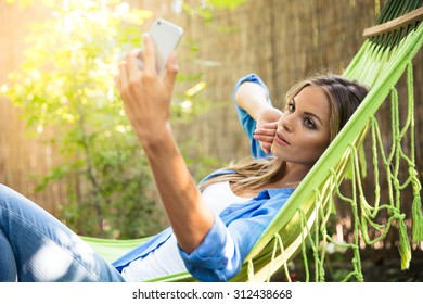 Woman lying on hammok and making selfie photo on smartphone outdoors