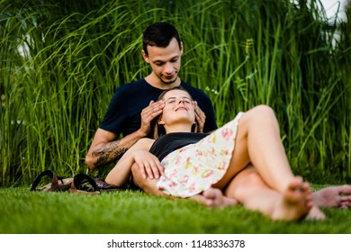 Woman lying on man's lap as he massages her forehead
