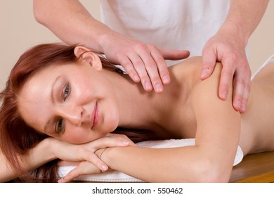 Woman lying on massage table with the hands of male masseuse on her back and shoulders
