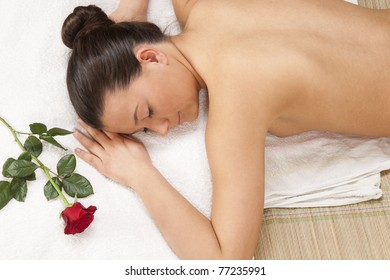 woman lying on massage table at spa resort with red rose