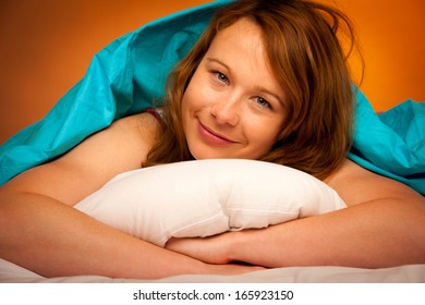 Woman lying on pillow in bed, covered with blue blanket