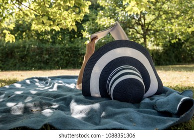 Woman lying on a rug in the shade of a tree spending a relaxing day in summer reading a book.
