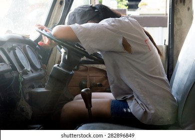 Woman lying on the steering wheel of the truck. Tired car driver sleep at the wheel. The interior of the old lorry with a female driver resting. Pause while driving.