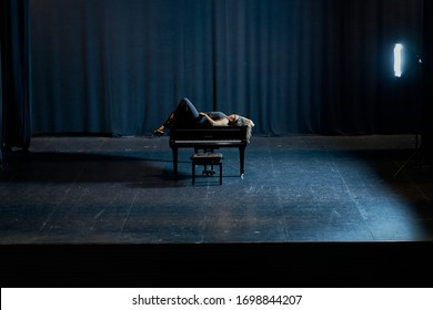 A woman lying on top of a grand piano on a stage
