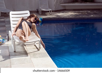A woman, lying in a pool chair, smiling and relaxing, dips her hand into the pool. - horizontally framed