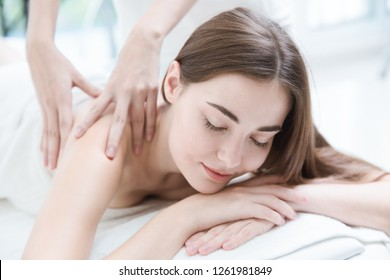 woman lying relax eyes close spa massage therapist massaging her shoulders white clean tone