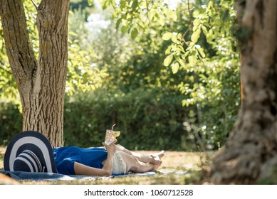 Woman lying relaxing in the shade of a tree in a  garden  in summer with a glass of water in her hand.
