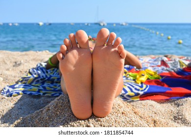 Woman lying in the sun with her feet facing the camera and her head towards the sea, vacation.