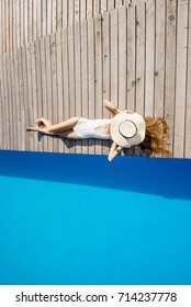 Woman lying with sunhat on the poolside near the basin with blue water. Geometric top view with copy space