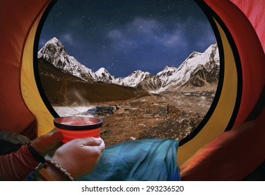 Woman lying in a tent with coffee ,view of mountains and sky in Gorak Shep village - Nepal, Himalayas