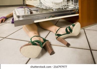 Woman lying under a dishwasher.