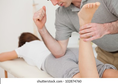 Woman lying while being massaged by her doctor in a room