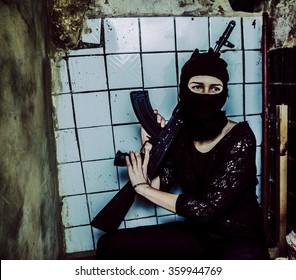 woman with a machine gun. Girl wear black mask