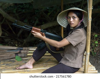 Woman with a machine gun sits in a bamboo shelter.Asian woman with a Kalashnikov in the village. Asian woman guard with a machine gun in a bamboo hut. Armed Asian woman. Asian patrol.