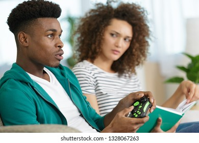 woman is mad with boyfriend because he plays video games