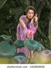 Woman in a magic garden. Concept of fairy tales, mistical book cover. Girl like princess in a purple long dress holds lotos flower