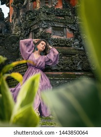 Woman in a magic garden. Concept of fairy tales, mistical book cover. Girl like princess in a purple long dress