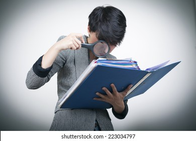 Woman with magnifying Glass Looking at Files / Investigation concept / Checking Law Case Concept / Detective Concept