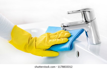 Woman maid or charwoman cleaning modern new basin in bathroom banner. Water tap clean using yellow gloves and blue cloth.