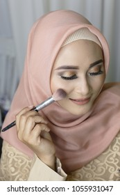 woman make up brushes using muslim jilbab for beauty face. Beautiful girl with cosmetic powder brush for make up. Makeup. Make-up applying for perfect skin.  yogyakarta indonesia. march 26, 2018.