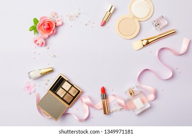 woman make up cosmetics on purple. Decorative cosmetics: highlighter, concealer, rouge, palette with eye shadows and brushes for face make up, face sculpture. Copy space. Gold and purple