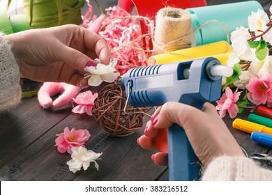Woman make floral decor with melt glue gun
