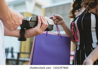 woman make payment with credit card swipe through terminal. customer paying with EDC or swiping machine. buy and sell product or service