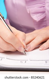 Woman make plans - hand with pen take a note in diary.