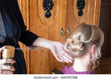 Woman makes a hairstyle to bride. Closeup of hairstyle, hairspray.