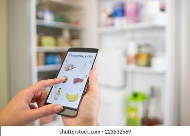 Woman makes her shopping list on his phone connected to the refrigerator