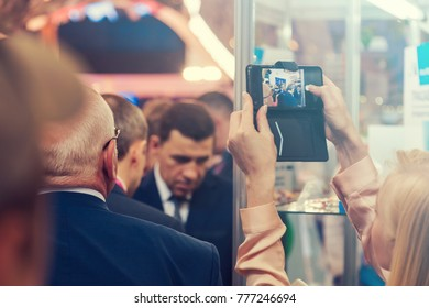 woman makes a photo on a smartphone at an exhibition