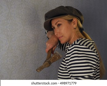 the woman makes the repair of an apartment / the woman with a hammer