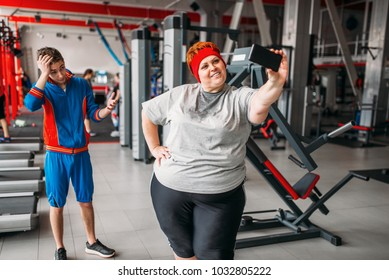 woman makes selfie with instructor in gym