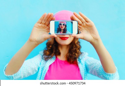 Woman makes self-portrait on smartphone view screen over colorful blue background