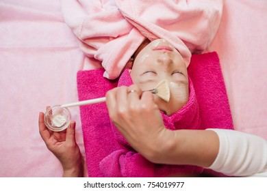 Woman makes spa procedures for a little girl in pink bath robe lying on the table