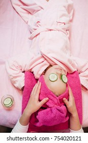 Woman makes spa procedures for a little girl in pink bath robe with cucumbers on her eyes lying on the table