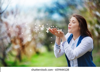 A woman makes a wish, blowing off the petals of flowers from her palms. She is full of hope, standing in the midst of a blooming apricot garden