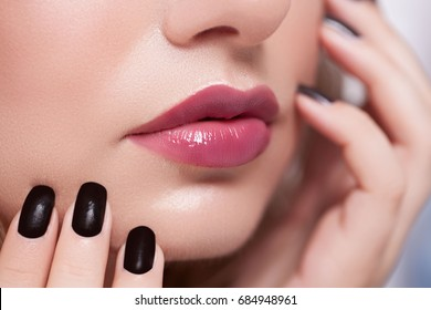 Woman Makeup and Manicure. High Fashion Model Girl Portrait with Trendy Hair style, Make up and Manicure. Black Matte Nail Polish and Red Matte Lipstick. Sexy Lips.
