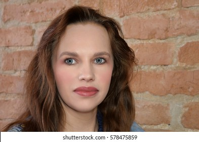 woman in makeup to the wall with bricks