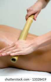woman making a bamboo massage in the back