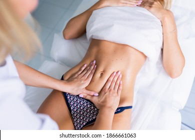 A woman making a belly massage in light procedure room. Anti-cellulite massage, diastasis. Faces are not recognizable