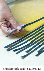 Woman making black and white striped farfalle or bowtie pasta. Step by step process of making homemade stripe pasta with squid ink.See series.