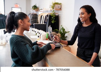 Woman making card payment at the counter in a clothing store