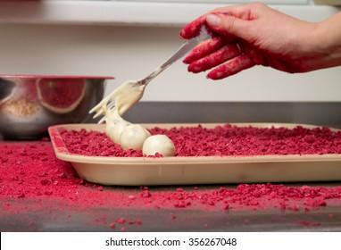 Woman making chocolate truffles with raspberry.