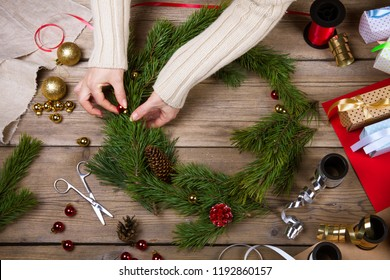 Woman making Christmas wreath. Top view