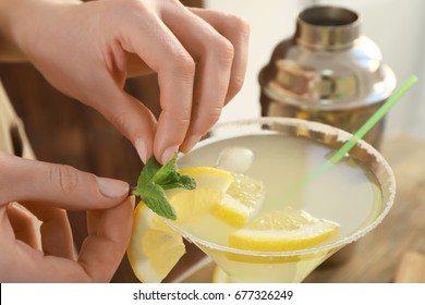 Woman making cocktail with tequila, closeup