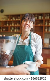 woman making coffee and giving it to customer