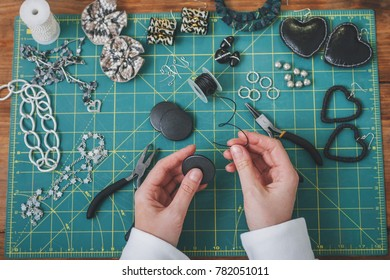 Woman making costume jewelry. Top view