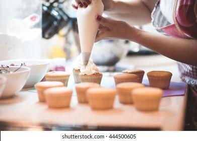 Woman making creamy top of cupcakes closeup. Selective focus.