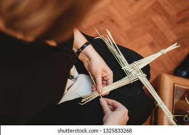 Woman making cross from straw